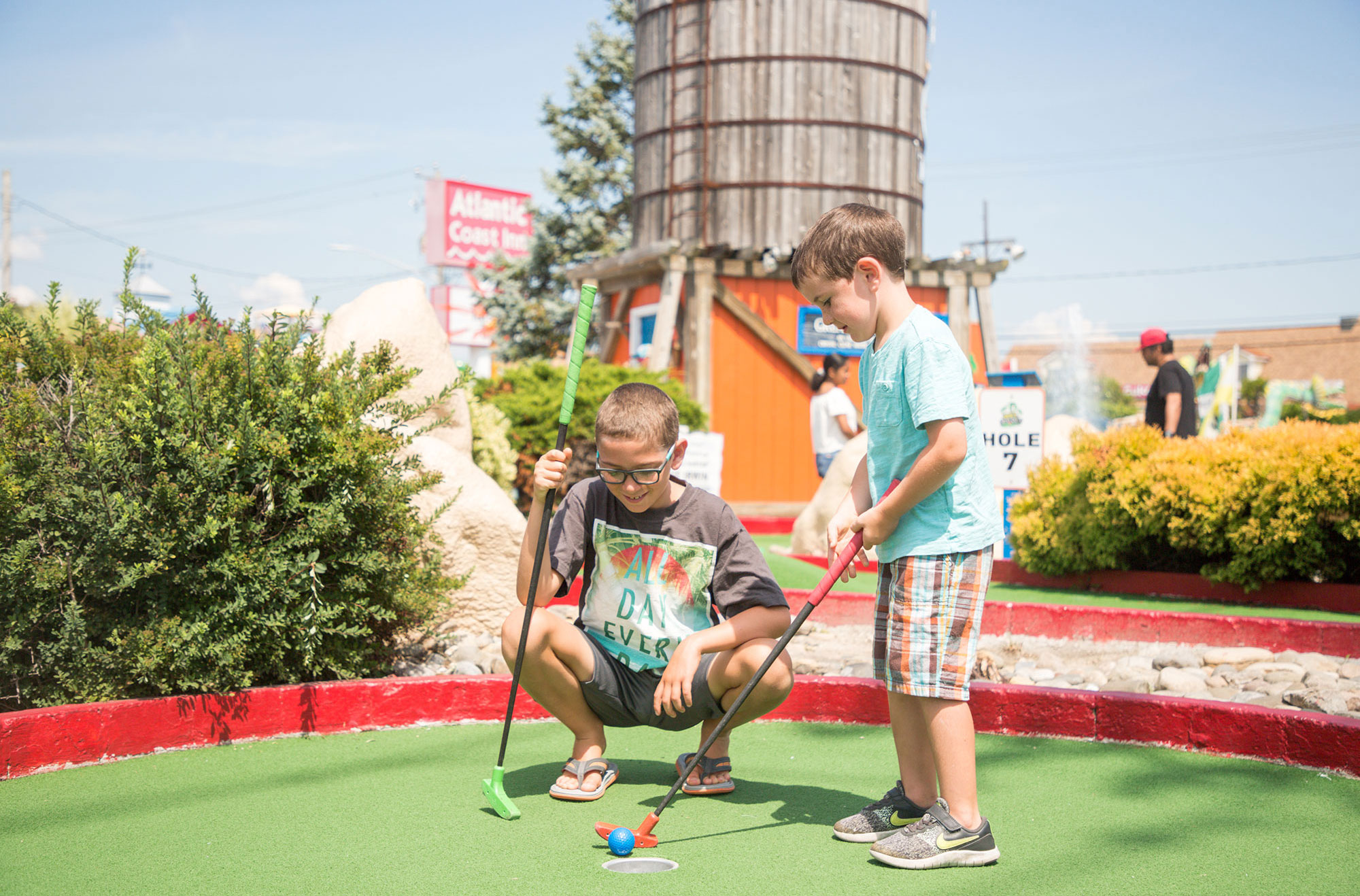Young boys golfing on the mini golf course